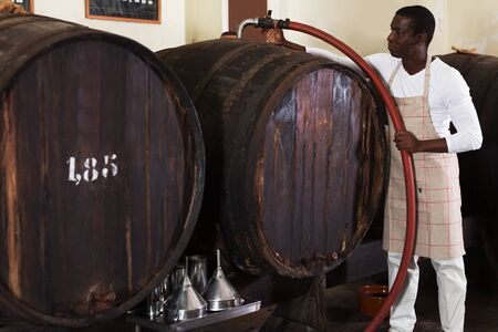 Confident male winemaker working in wine-vault, filtering wine in barrels Banque d'images - 139312208