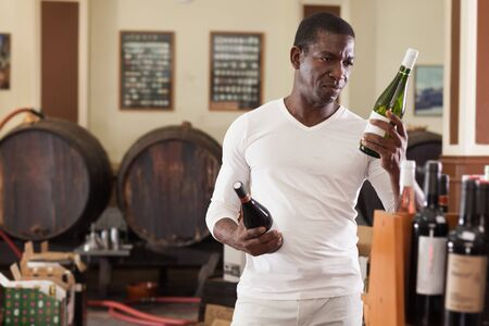 Portrait of young African American man visiting winehouse searching a bottle of good wine Banque d'images - 139313856