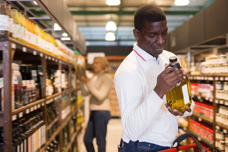Hombre afroamericano adulto haciendo compras en la tienda, eligiendo aceite vegetal Foto de archivo