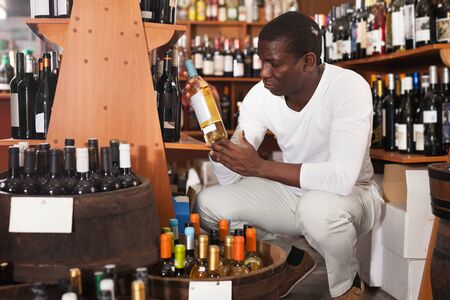 Portrait of young African American man visiting the winehouse searching bottle of a good wine Banque d'images - 139312022