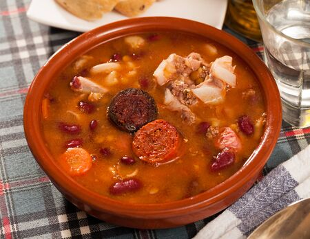 Delicious Fabada asturiana with stewed beans, pork, morcilla and chorizo served in traditional clay cazuela