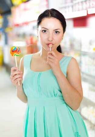 Young woman  sucking lolly  in candies shop Stock Photo