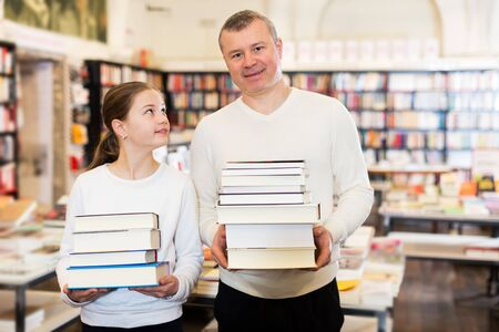 Happy little girl with her loving father holding pile of books bought in bookshop