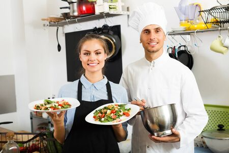 glad cook in uniform standing with waitress and served fresh green salad on kitchen