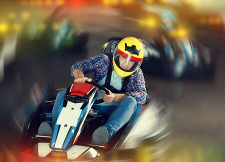 Glad cheerful positive smiling male in helmet and other people driving cars for karting in sport club indoor