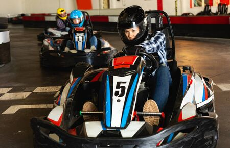 Youn woman in helmet driving car for karting with other people in sport club indoor