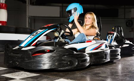 Cheerful blonde smiling young girl posing with helmet in her hands at kart circuit