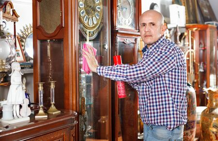 Middle aged diligent positive cheerful man owner of antiques shop wiping vintage goods