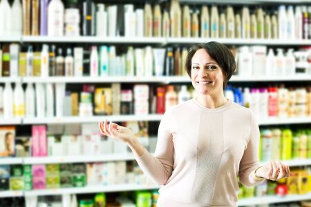 Smiling female customer buying conditioner for hair in supermarket