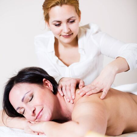 Young masseuse massaging shoulders and neck of mature woman in massage salon. Selective focus on hands