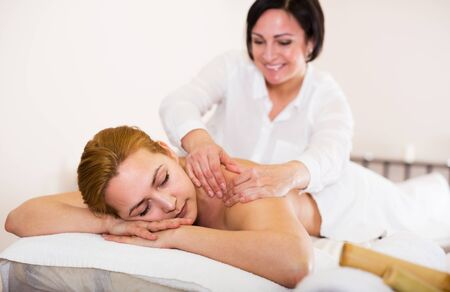Adult masseuse massaging shoulders and neck of young woman in massage salon Imagens