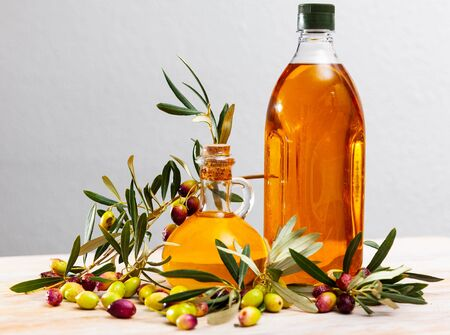 Organic olive oil in decanters and bottles and fresh olives on wooden table