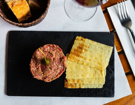 Delicious meaty tartare made of raw veal garnished with crispy flatbread