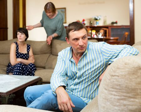 Adult man and her wife with her senior mother after quarrel at home