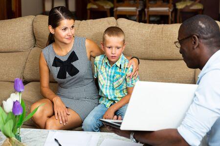 Une femme et son petit fils rencontrent un agent immobilier afro-américain chez elle Banque d'images