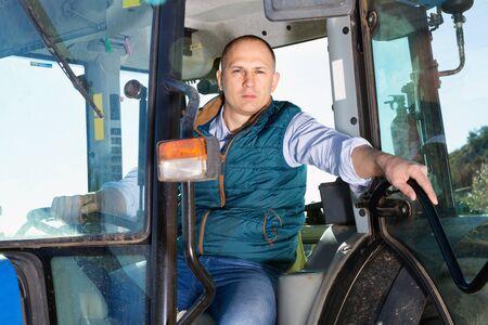 Portrait of cheerful glad handsome man working on farm tractor in vineyard