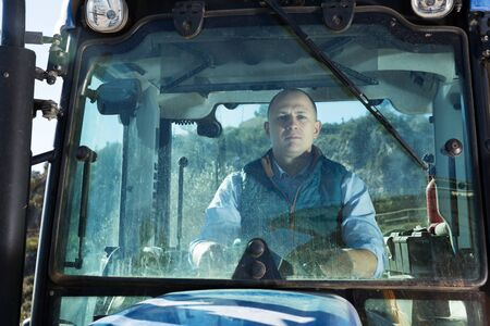 Portrait of positive male working in vineyard sitting in tractor cab Portrait of confident male working in vineyard sitting in tractor cab
