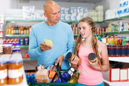 adult father doing shopping with preteen girl in food department of supermarket Stock Photo