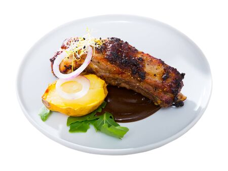 Roasted spicy pork ribs served on white plate in chocolate sauce with baked potatoes and greens. Isolated over white background