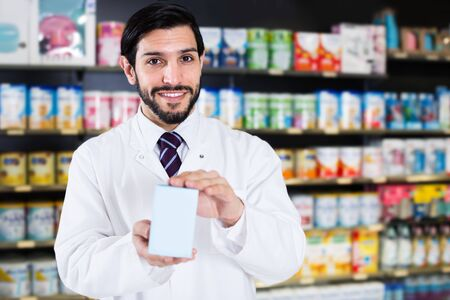 Smiling male pharmacist is standing with medicines in drugstore Stockfoto