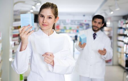 Portrait of glad female specialist who is holding medicines near shelves in pharmacy