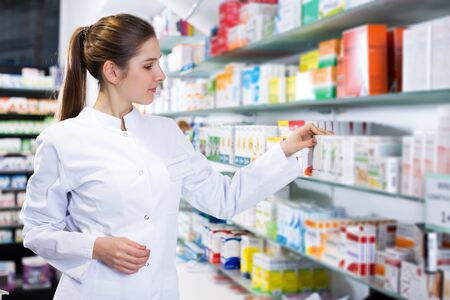 young woman pharmacist is searching medicine on shelves in apothecary.