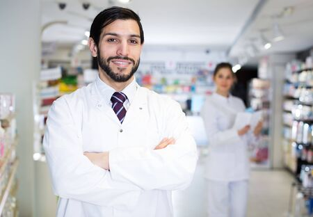 Portrait of male pharmacist who is standing on his work place in apothecary.
