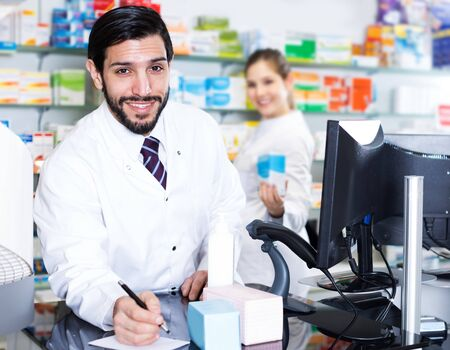 Positive man pharmacist is writing to note inventsry of medicines near computer in drugstore Stockfoto