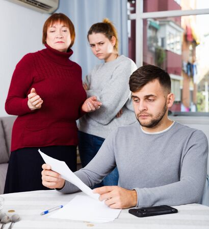 Portrait of distressed man with paperwork at home table with irritated family behind him