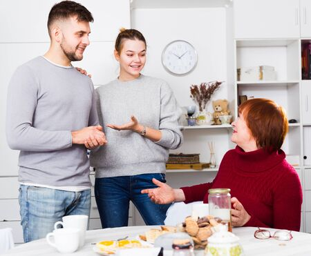 Happy girl introducing her boyfriend to elderly mother at home