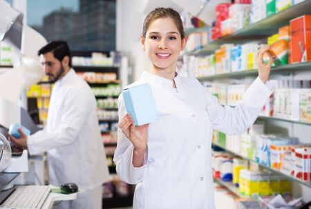 Smiling woman pharmacist is searching medicines on shelves in drugstore