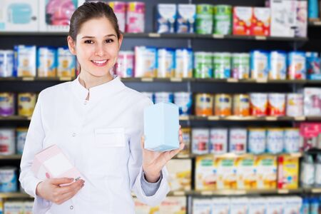 Smiling woman pharmacist is standing with medicines in drugstore