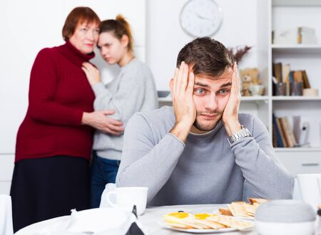 Young upset man sitting separately having problems in relationship with wife and her mother