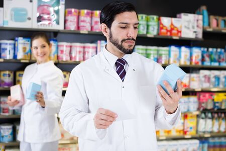 Adult male specialist who is holding medicines near shelves in pharmacy