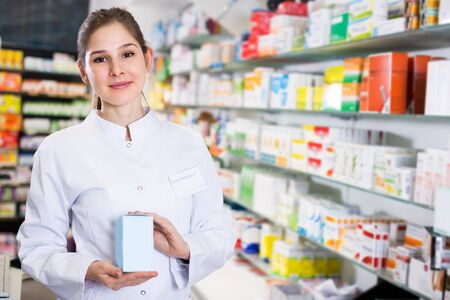 Positive woman pharmacist is standing with medicines in pharmacy