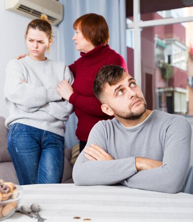 Young man sitting at home table offended after quarrel with mother and sister