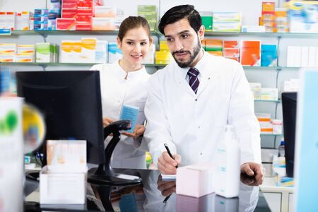 Two diligent serious positive pharmacists are attentively stocktaking medicines with computer and note on paper in pharmacy.