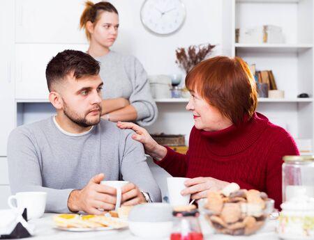 Senior woman calming upset guy during his quarrel with girlfriend Stock Photo
