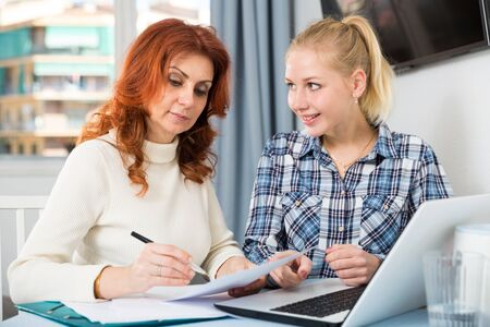 Woman and adult daughter fill out paperwork Stock fotó