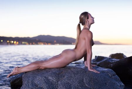 Nude young positive woman is lying on a rock near the sea at the dawn.
