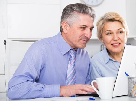 Mature colleagues look at screen of laptop and discuss documents