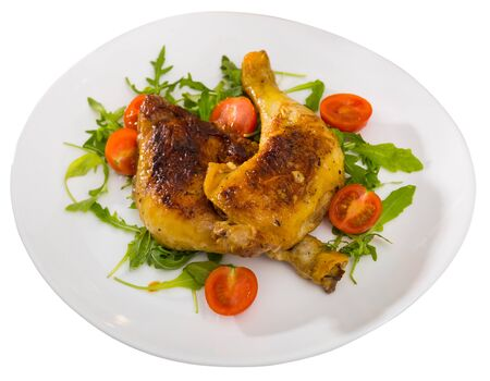 Fried chicken legs with arugula and tomatoes. Isolated over white background