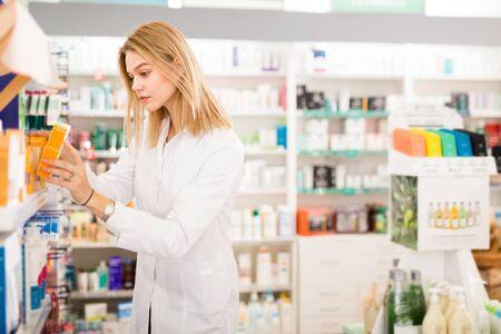 Jonge ijverige vriendelijke glimlachende vrouwelijke apotheker die het weergegeven assortiment in de farmaceutische winkel regelt