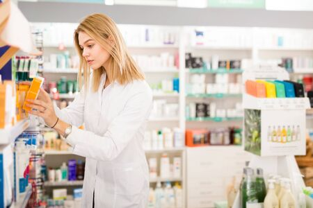 Young diligent friendly smiling female pharmacist arranging displayed assortment in pharmaceutical store