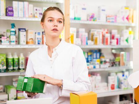 Farmacéutico joven mujer positiva que trabaja en la tienda farmacéutica Foto de archivo