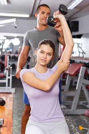 Homme sportif coachant une fille et expliquant la technique des exercices avec des haltères au gymnase