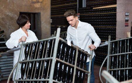 Smiling male worker transporting wine bottles to storage at sparkling wine factory