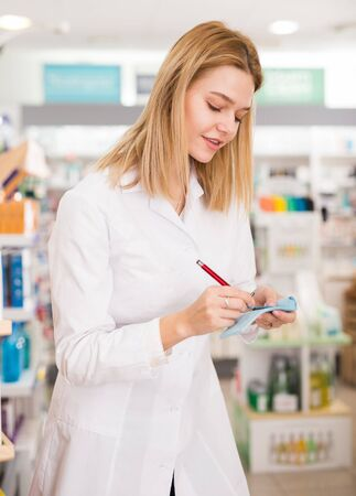 Smiling female pharmacist checking assortment of drugs in pharmacy
