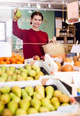 Chica morena feliz comprando piña madura en el supermercado Foto de archivo
