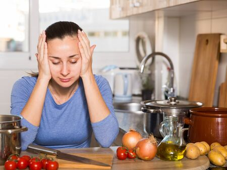 Portrait of sad and tired woman cooking vegetable soup at kitchen
